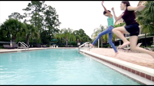 Preteen girls jumping into swimming pool