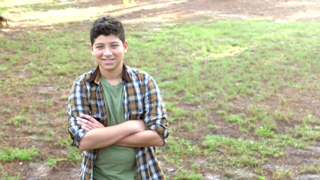preteen hispanic boy standing in park - plaid shirt stock videos & royalty-free footage