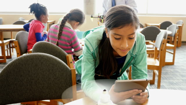 Pre-teen Hispanic female student uses digital tablet to control robotic helicopter in STEM school library