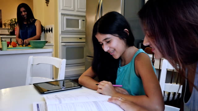 preteen hispanic girl doing homework with help of big sister while mother prepares dinner - brace stock videos and b-roll footage