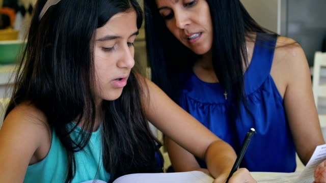 Preteen home school student writing during science class with mother