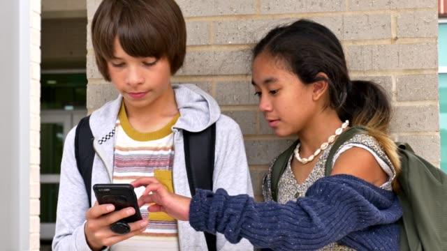 preteen junior high students use smartphone on the school campus - preadolescente video stock e b–roll