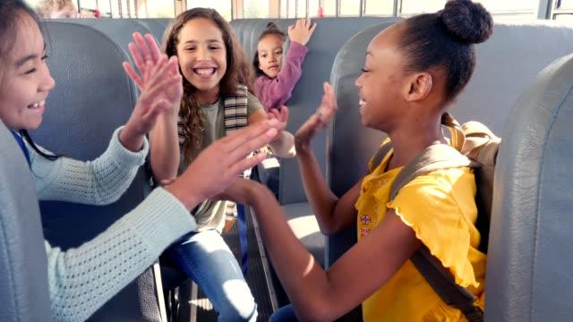 vídeos y material grabado en eventos de stock de preteen niñas de la escuela juegan juego de aplaudiendo mano en el autobús escolar - educación