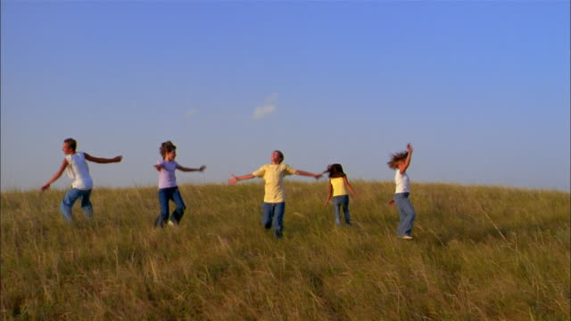 Preteens run and spin with outstretched arms through a grassy field.