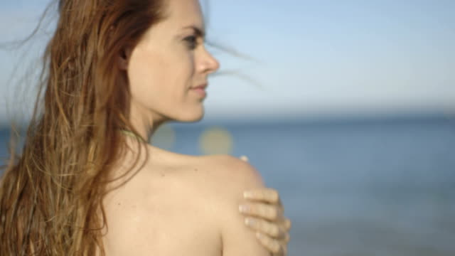 pretty adult female in bikini applying sun cream - langes haar stock-videos und b-roll-filmmaterial