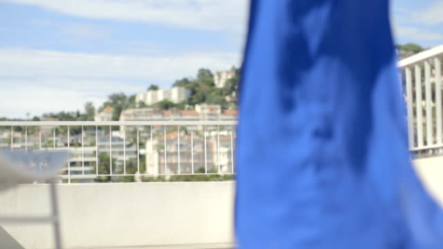 Pretty adult female in blue dress walking on terrace