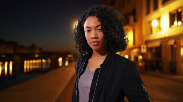 Pretty African American Millennial woman standing outdoors in Florence at night