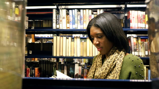 Pretty African American young female teacher searches for book in local public library