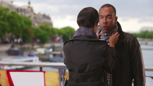 Pretty African girlfriend fixes up boyfriend's outfit on cold day in Paris