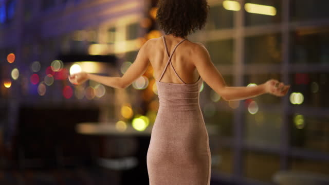 Pretty African woman spinning body indoors.  Attractive woman showing off curvy body inside casino.