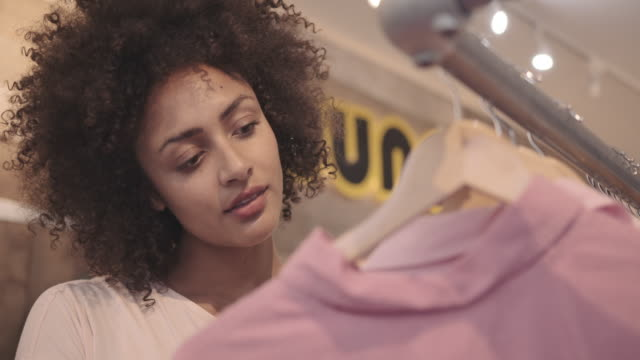 pretty afro american female customer looking at vintage clothes in shop - shopaholic stock videos & royalty-free footage
