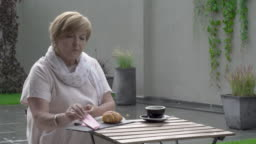 A pretty aged woman is eating a croissant and drinking tea. She sit in the terrace. It's raining.
