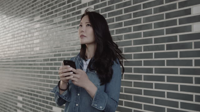 pretty asian female looking at smart phone and look for taxi on urban road in city - korean ethnicity stock videos & royalty-free footage
