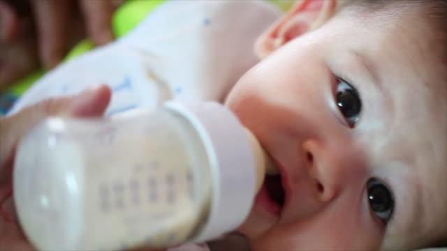 pretty baby boy drinking milk from bottle - milk bottle stock videos & royalty-free footage