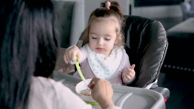 vidéos et rushes de la jolie fille de chéri mange les céréales instantanées du bol sur le plateau élevé de chaise - céréale