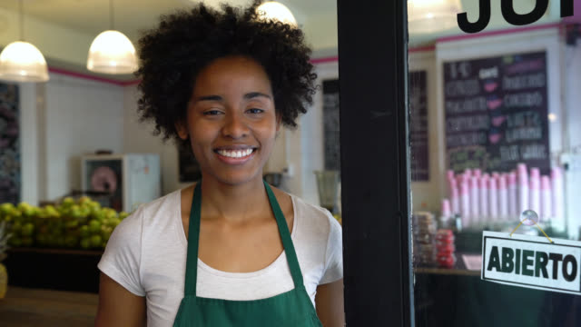 Pretty black business owner at her restaurant looking at the camera smiling