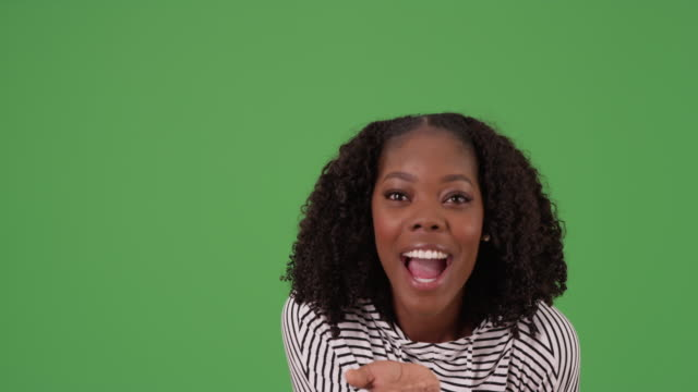 pretty black female in striped sweatshirt blows kisses at camera on greenscreen - {{asset.href}} stock videos & royalty-free footage