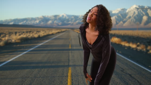 vídeos y material grabado en eventos de stock de pretty black female jogger taking break along road in mountain landscape - corredora de footing