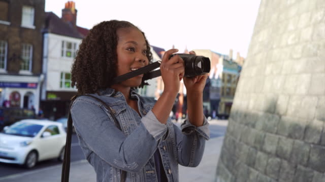 vídeos de stock, filmes e b-roll de pretty black female on urban street in england takes photo with camera, smiling - jaqueta jeans