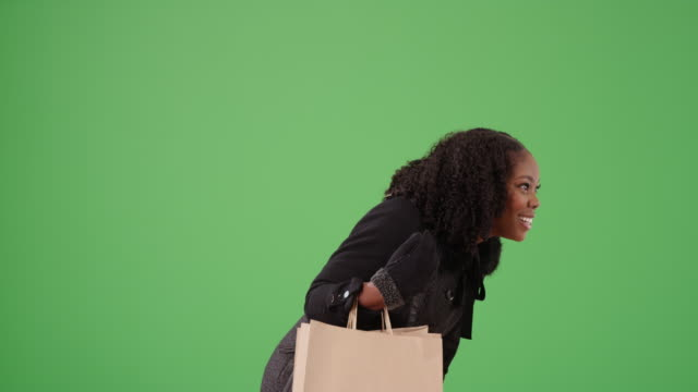 pretty black female shopping, bending down to look at something on green screen - {{ contactusnotification.cta }} stock videos & royalty-free footage