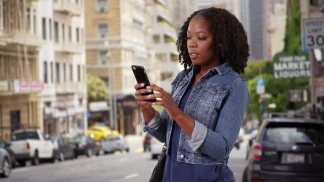 vídeos de stock, filmes e b-roll de pretty black female smiles at cute text from boyfriend on urban street - jaqueta jeans