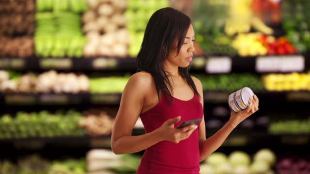 Pretty black female takes photo of nutrition label on tuna can at supermarket