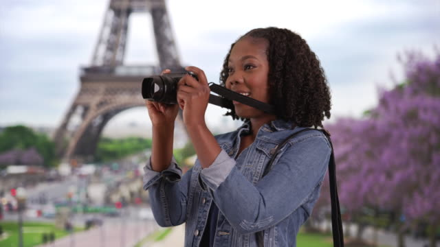 pretty black female takes picture in paris, view of eiffel tower in background - african american culture stock videos & royalty-free footage