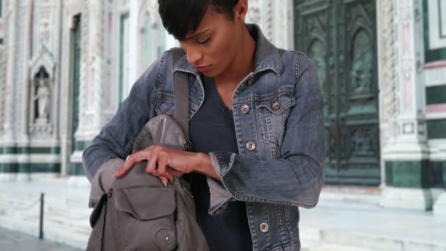 vídeos y material grabado en eventos de stock de pretty black woman rummaging through handbag outside florence cathedral - en búsqueda