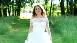 Pretty bride walks at camera in the sunny park. Slowly