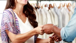 Pretty brunette paying with card at clothing store