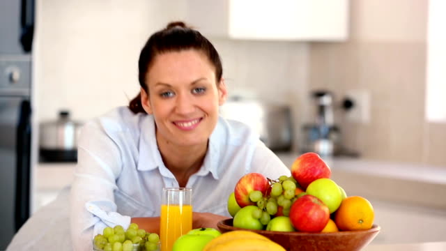 pretty brunette smiling at camera behind fruit - ascorbic acid stock videos and b-roll footage