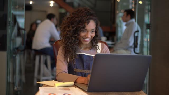 hübsche eigentümer von restaurant tun die bücher mit einem laptop und lächelnd - gastwirt stock-videos und b-roll-filmmaterial