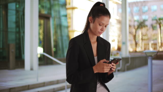 Pretty business woman wearing blazer downtown texting on mobile phone