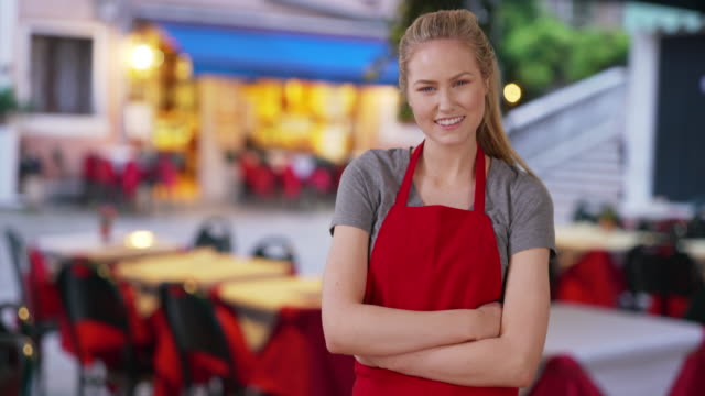 pretty caucasian caterer posing and standing outside near some tables - caterer stock videos and b-roll footage