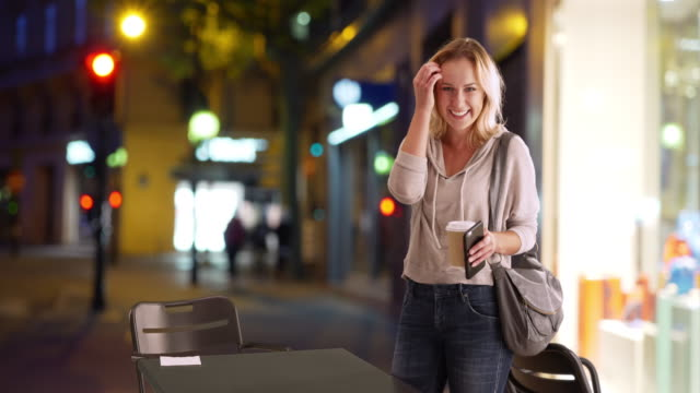 pretty caucasian female holding phone and coffee cup near table in city setting - hip stock videos & royalty-free footage