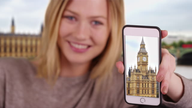 pretty caucasian girl showing picture of big ben clock tower on smartphone - big ben点の映像素材/bロール