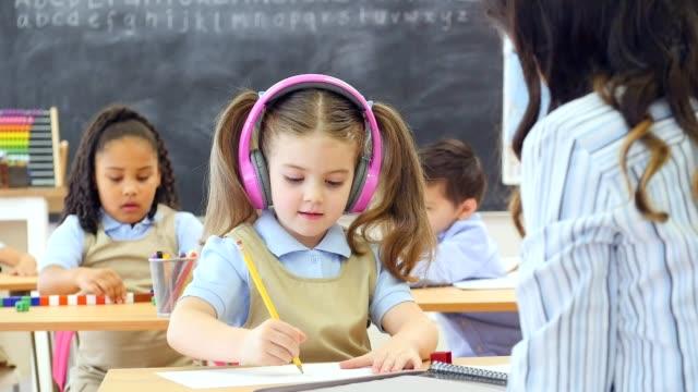 Pretty Caucasian preschool student wears wireless headphones at school