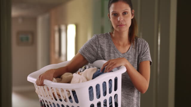 pretty caucasian woman at home holding basket of clean clothes - halten stock-videos und b-roll-filmmaterial