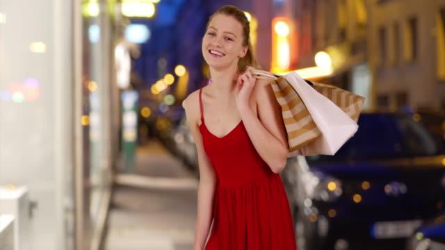vidéos et rushes de pretty caucasian woman holding shopping bags on city street smiling - robe d'été