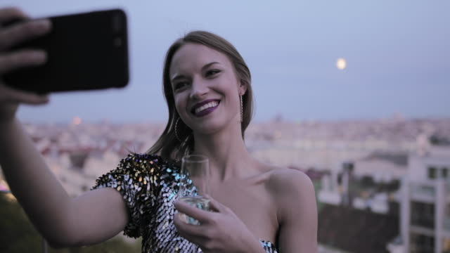 pretty caucasian woman on rooftop taking selfie at sunset in cocktail dress - cocktail dress stock videos & royalty-free footage
