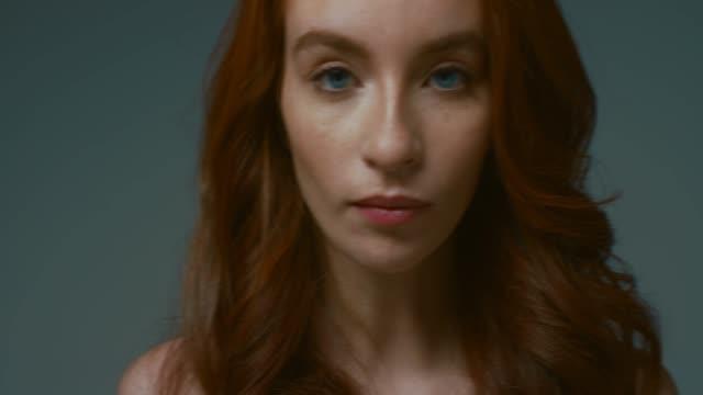 stockvideo's en b-roll-footage met pretty vrolijke roodharige meisje lacht op de camera op grijze achtergrond - roodhoofd