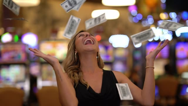 pretty cheerful woman throwing money to the air after a lucky strike in the casino - lanciare video stock e b–roll