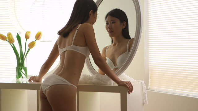 Pretty Chinese woman looking at mirror