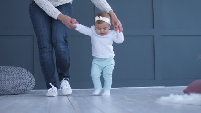 Pretty daughter learning to walk and holding hands of mother