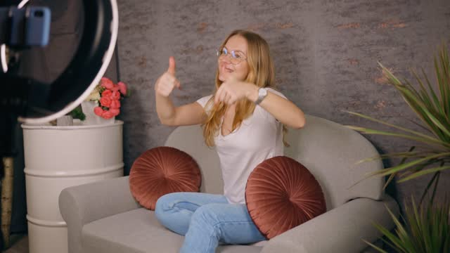 pretty female blogger live streaming her content asking to subscribe - content stock-videos und b-roll-filmmaterial