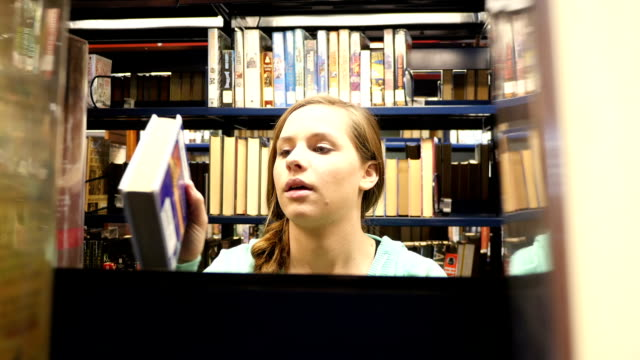 pretty female caucasian home school high school student searches for book in public library - braided hair stock videos & royalty-free footage