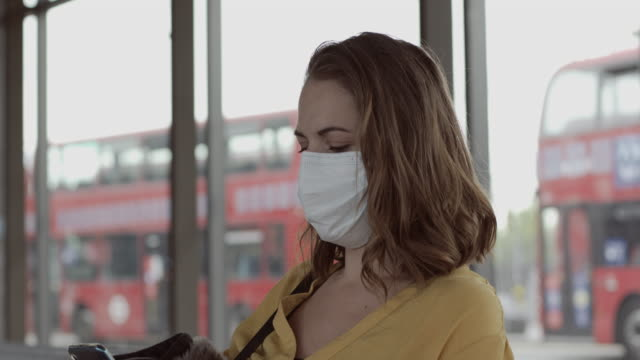 pretty female in airport bus terminal wearing protective face mask using smart phone during covid19 pandemic - bus stock videos & royalty-free footage