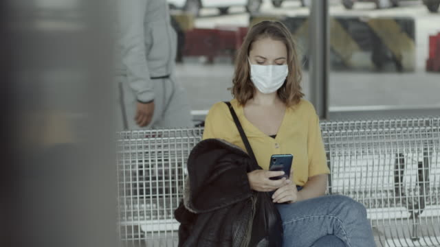 pretty female in airport bus terminal wearing protective face mask using smart phone during covid19 pandemic - endurance stock videos & royalty-free footage