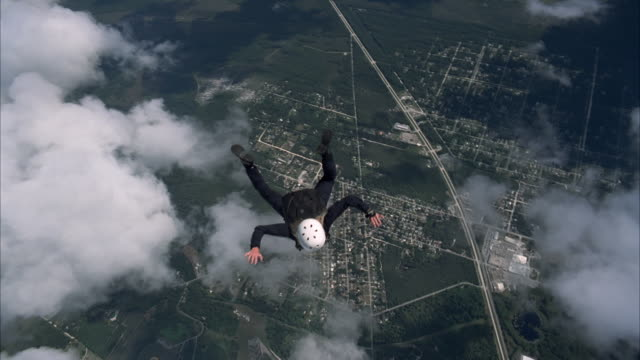 pretty female skydiver falls past clouds - airplane part stock videos and b-roll footage