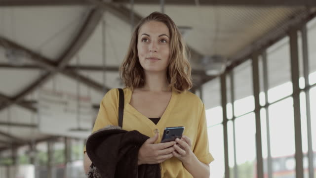 pretty female standing in airport terminal using smart phone and waiting for flight - railway station stock videos & royalty-free footage